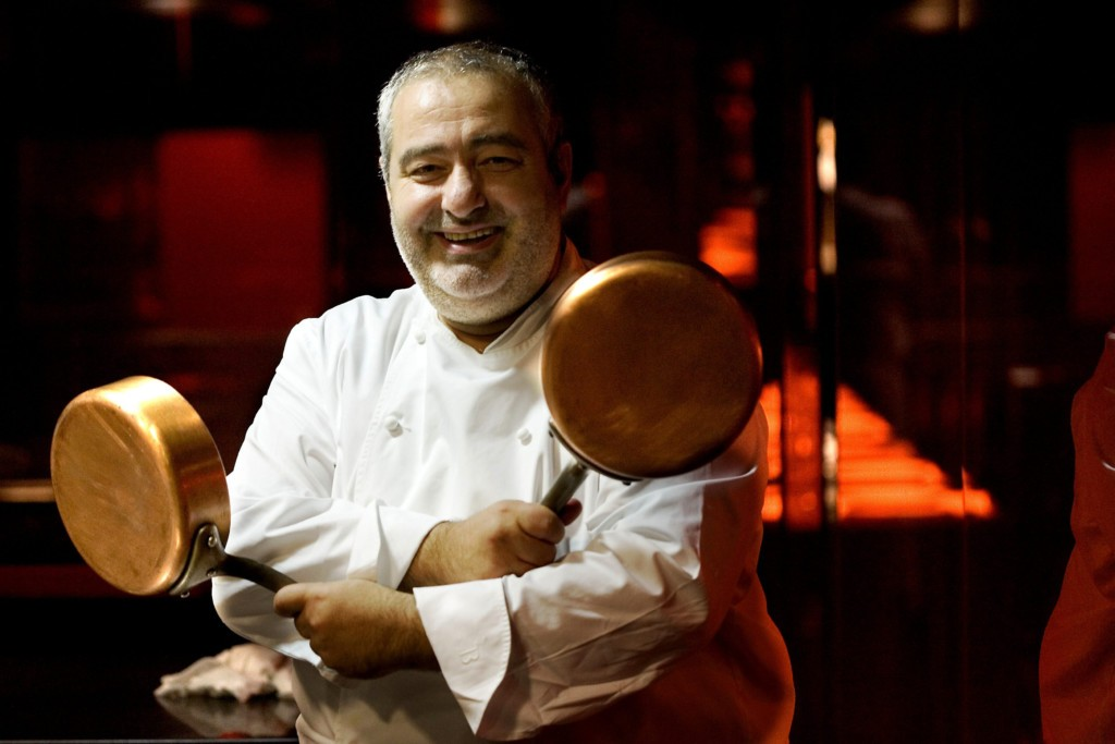 Chef Santi Santamaria with two pans in hand in cooking uniform
