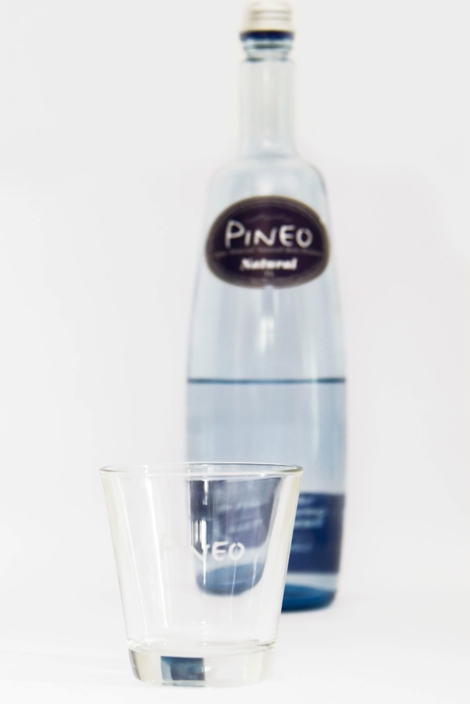 Pineo water bottle with glass in the foreground