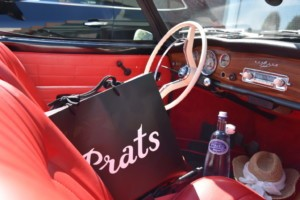 The inside of an old timer car with a bag of prats and a bottle of pineo water