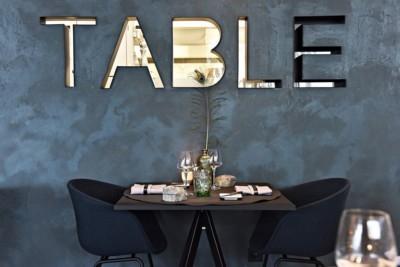 Een tafel met 2 zwarte stoen bij Chef's Table in Burcht