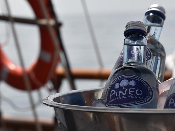 The durable glass bottles of Pineo in an ice bucket on a classic sailing ship during Sotogrande